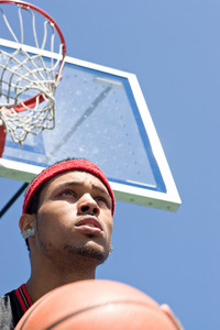A basketball player holding the ball underneath the backboard and hoop.