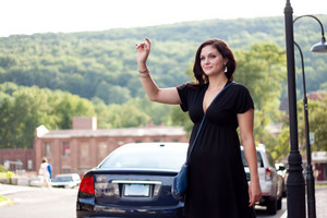 A beautiful brunette woman waving her arm tries to hail a cab at the side of the road in the city.