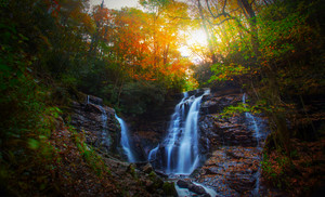 A beautiful waterfall in the forest with autumn leaves