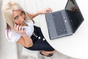 A beautiful young blond woman in a mobile business setting with her cell phone and laptop.