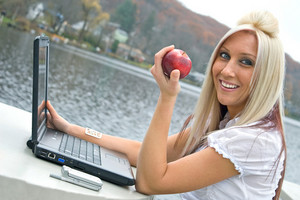 A beautiful young blonde woman in a mobile business setting eating a red apple while using her laptop notebook computer.