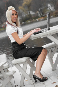 A beautiful young blonde woman in a mobile business setting with laptop and cell phone.