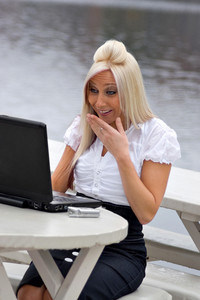 A beautiful young blonde woman is shocked by what she is seeing on her laptop screen.  It looks as if she is possibly seeing something offensive.