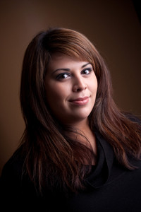 A beautiful young Hispanic woman with a smile on her face and highlighted hair.