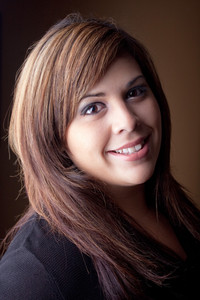 A beautiful young Latin woman with a smile on her face and highlighted hair.