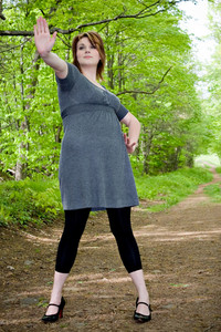 A beautiful young woman holding her hand up in front of herself as if to stop any on comers from entering the wooded trail.
