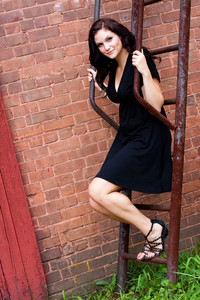 A beautiful young woman in her twenties posing in a run down urban setting on a rusted ladder or fire escape.