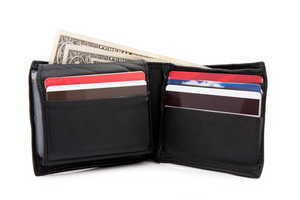 A black leather wallet with a few dollars and a bunch of credit cards isolated over white.