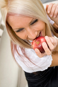 A blond business woman biting into a fresh apple on her lunch break.
