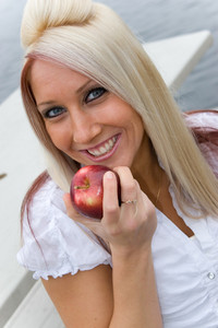 A blond business woman eating an apple on her lunch break.