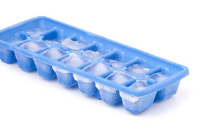 A blue plastic ice cube tray with frost on it isolated over a white background.
