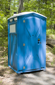 A blue porta potty located on the hiking trail
