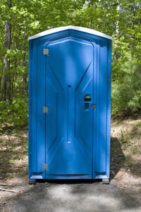 A blue porta potty located on the wooded hiking trail.