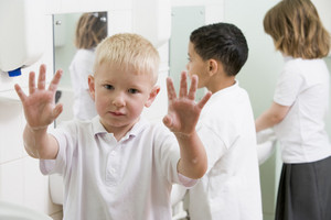 A boy displaying his hands in a primary school bathroom