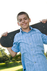 A boy in his early teens happily posing with his skateboard.