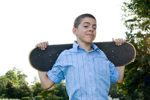 A boy in his early teens happily standing with his skateboard.