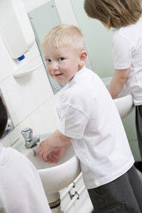 A boy washing his hands in a primary school bathroom