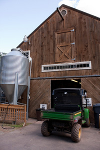 A brown wooden barn with a large grain silo tank outside.