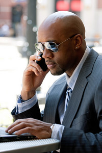A business man in his early 30s talking on his cell phone and working on his laptop or netbook computer.