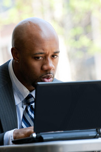 A business man in his early 30s working on his laptop or netbook computer outdoors with a surprised or shocked expression on his face.