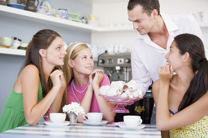 A cafe waiter offers young women teacakes
