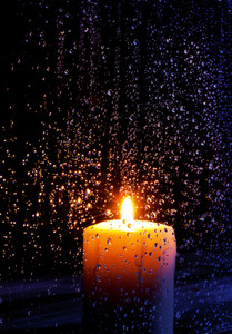A candle lit at night during a storm.