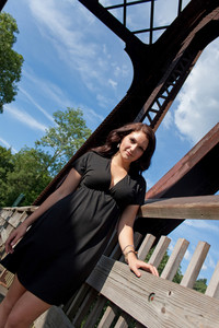 A carefree brunette woman hanging out along an old rusted walking bridge.