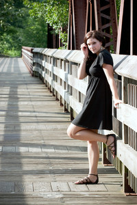 A carefree brunette woman hanging out along an old walking bridge.