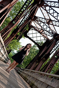 A carefree brunette woman walking along an old rusted bridge.