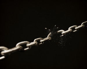 A chain on a black background breaks