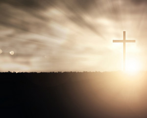 A Christian cross at sunset with light flares.