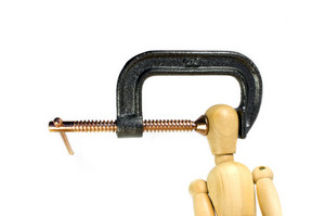 A clamp squeezing tightly on the head of a wooden man.  A great concept shot for headaches or stress.