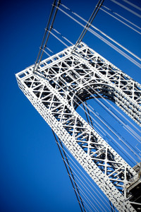 A close up portion of the large gate and metal detail on the New York City George Washington Bridge as seen from below.