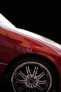 A closeup of a chrome rim on a modern luxury sedan, isolated over black.