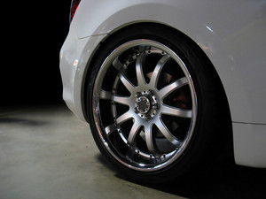 A closeup of a custom rim on a white sports car.