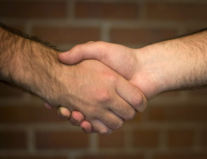 A closeup of a handshake between two business men over a brick wall backdrop.