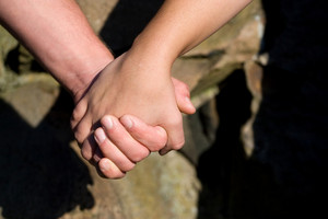 A closeup of a man and woman holding hands.