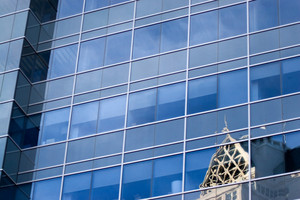 A closeup of a modern office building and another building visible in a reflection upon it.