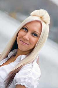 A closeup of a pretty blonde woman that is smiling.