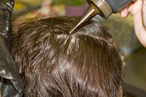 A closeup of a woman getting hair dye applied to her scalp.