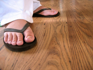 A closeup of a woman's feet wearing some black flip flops.