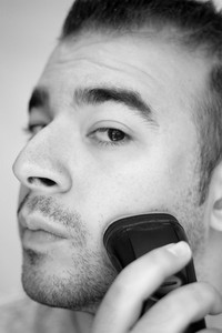 A closeup of a young man shaving his beard off with an electric shaver in black and white.
