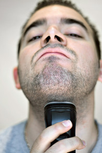 A closeup of a young man shaving his beard off with an electric shaver. Shallow depth of field.
