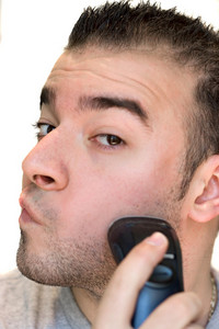 A closeup of a young man shaving his beard off with an electric shaver.