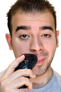 A closeup of a young man shaving his face with an electric shaver.