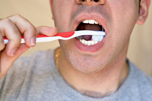 A closeup of a young man while he is brushing his teeth.