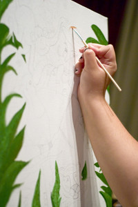 A closeup of a young woman painting on a canvas.