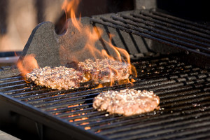A closeup of some fresh and juicy hamburgers cooking on the grill.