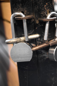 A closeup of some pad locks in use in an urban setting.