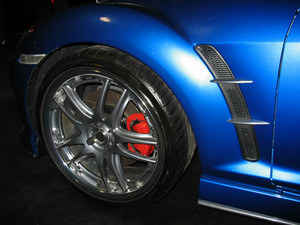 A closeup of the front quarter of a blue import sportscar.
